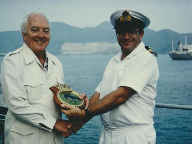 With the captain of HMS Starling in Hong Kong, receiving the ship's crest.