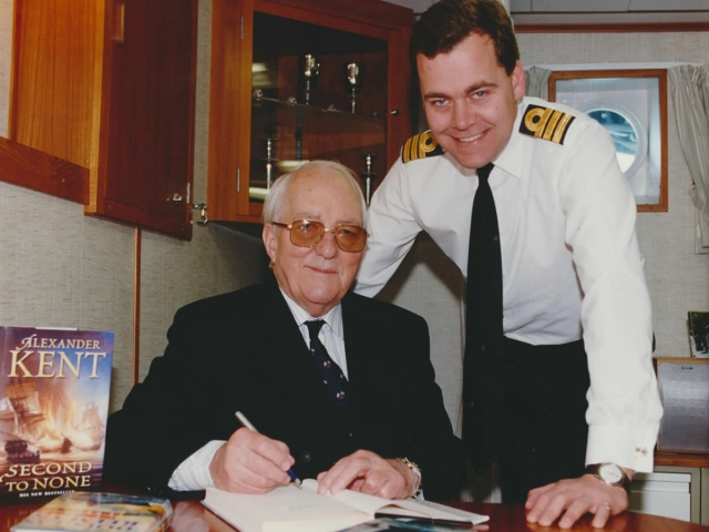 Douglas Reeman signing books during visit to HMS Kent in 2000 (photo courtesy Royal Navy).