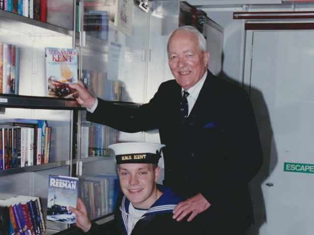 Presenting a collection of his books, with a Royal Navy rating, to the HMS Kent library in 2000 (photo courtesy Royal Navy).